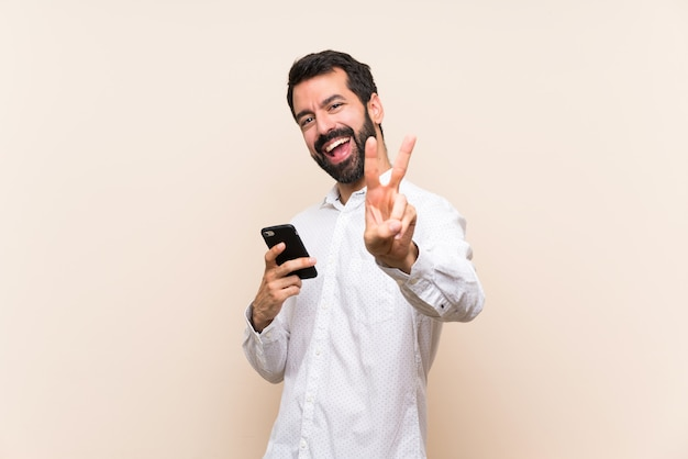 Young man with beard holding a mobile smiling and showing victory sign