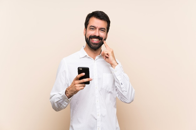 Young man with beard holding a mobile smiling with a happy and pleasant expression