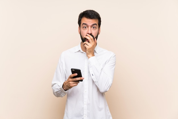 Young man with beard holding a mobile surprised and shocked while looking right