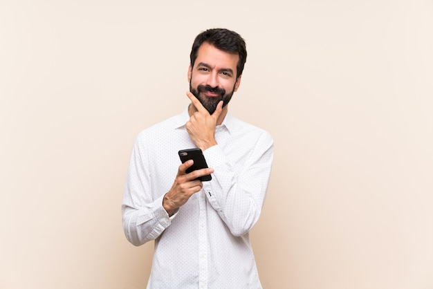 Young man with beard holding a mobile thinking
