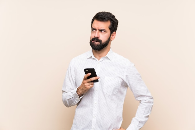 Young man with beard holding a mobile with confuse face expression