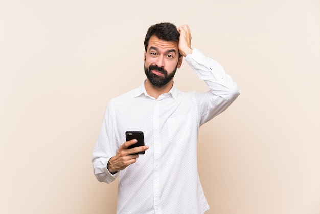 Young man with beard holding a mobile with an expression of frustration and not understanding