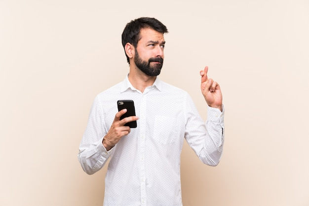Young man with beard holding a mobile with fingers crossing and wishing the best