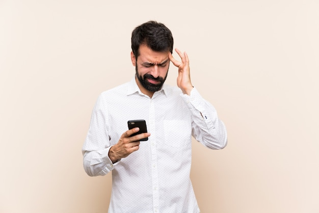 Young man with beard holding a mobile with headache