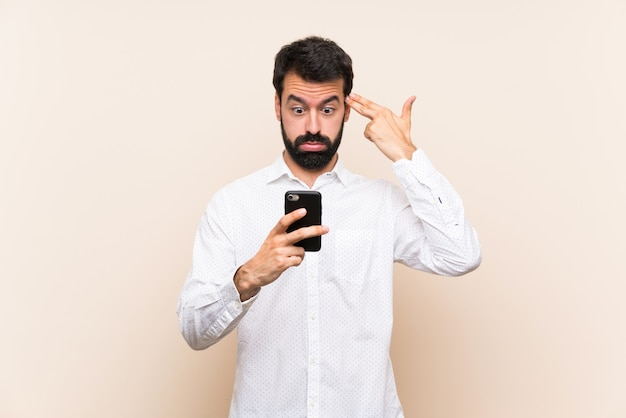 Young man with beard holding a mobile with problems making suicide gesture