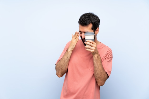 Young man with beard holding a take away coffee  on blue  covering eyes by hands