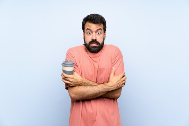 Young man with beard holding a take away coffee  on blue  freezing