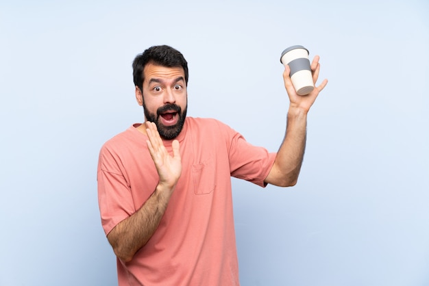 Young man with beard holding a take away coffee  on blue  nervous and scared