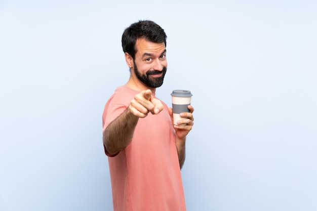 Young man with beard holding a take away coffee  on blue  points finger at you with a confident expression