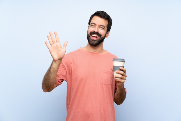 Young man with beard holding a take away coffee  on blue  saluting with hand with happy expression