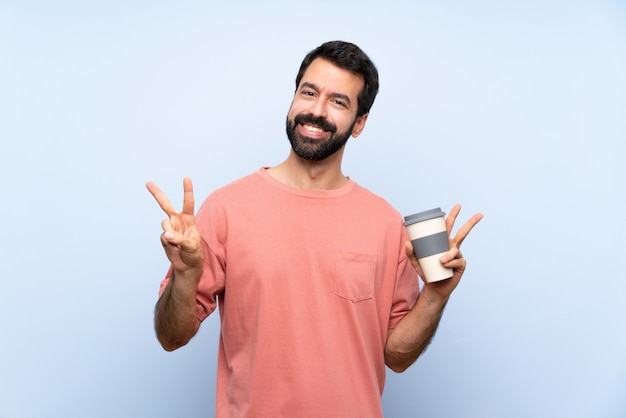 Young man with beard holding a take away coffee  on blue  showing victory sign with both hands