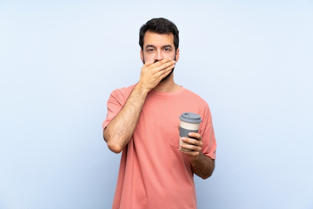 Young man with beard holding a take away coffee over isolated blue  covering mouth with hands