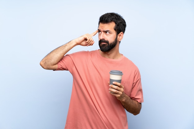 Young man with beard holding a take away coffee over isolated blue  having doubts and thinking