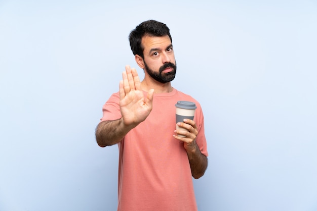 Young man with beard holding a take away coffee over isolated blue  making stop gesture