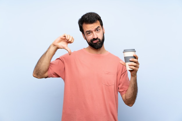 Young man with beard holding a take away coffee over isolated blue  showing thumb down