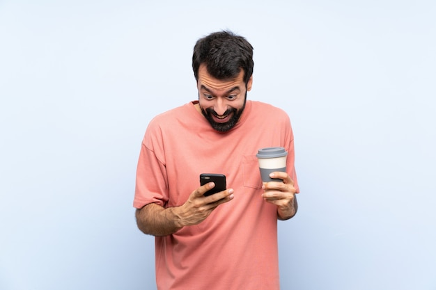 Young man with beard holding a take away coffee over isolated blue  surprised and sending a message
