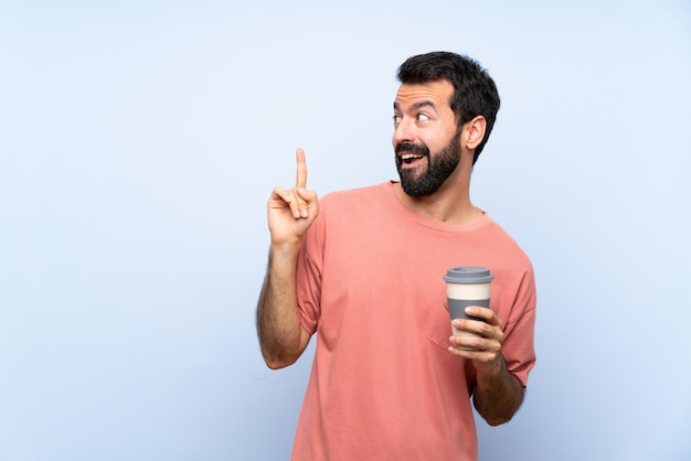 Young man with beard holding a take away coffee over isolated blue wall intending to realizes the solution while lifting a finger up