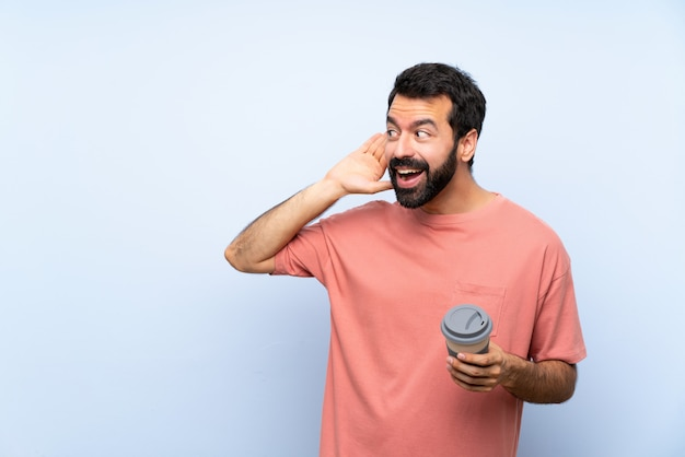 Young man with beard holding a take away coffee over isolated blue wall listening to something by putting hand on the ear