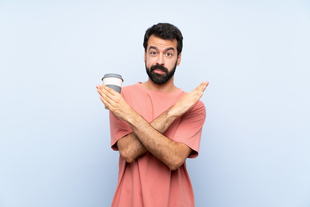 Young man with beard holding a take away coffee over isolated blue wall making no gesture