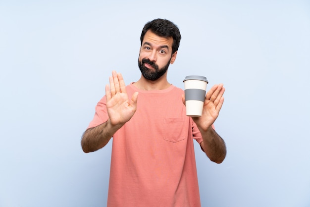 Young man with beard holding a take away coffee over isolated blue wall making stop gesture and disappointed