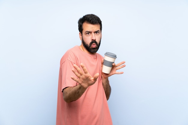 Young man with beard holding a take away coffee over isolated blue wall nervous stretching hands to the front