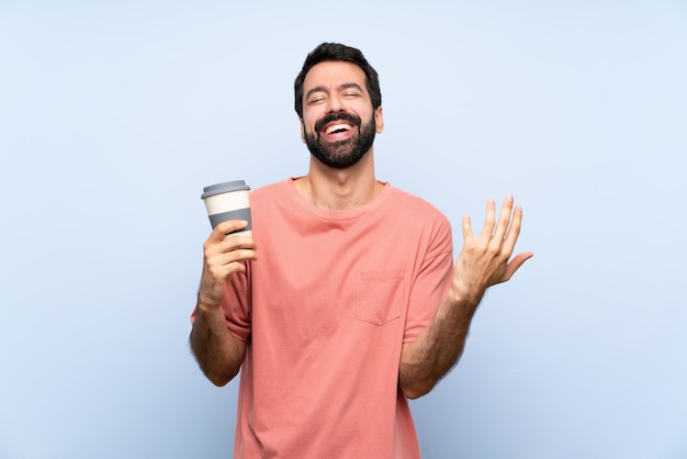 Young man with beard holding a take away coffee over isolated blue wall smiling a lot