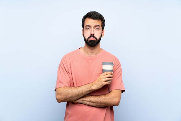 Young man with beard holding a take away coffee over isolated blue wall with sad and depressed expression