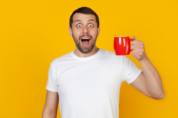 A young man with a beard holds a mug of coffee, opening his mouth in surprise