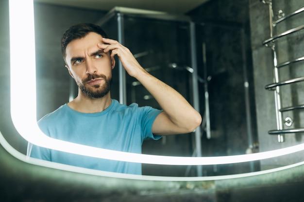 Молодой человек с бородой в синей футболке ищет прыщ на лице у зеркала в ванной, проблема прыщей