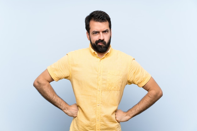 Young man with beard over isolated blue  angry