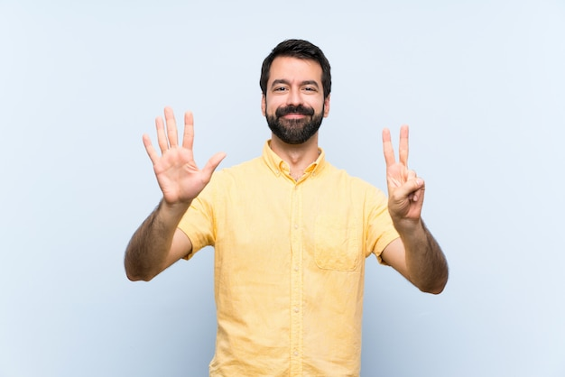 Young man with beard over isolated blue   counting seven with fingers