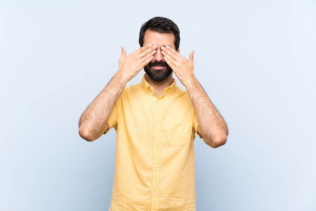 Young man with beard over isolated blue  covering eyes by hands