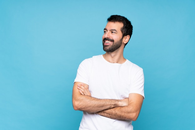 Young man with beard  over isolated blue  happy and smiling