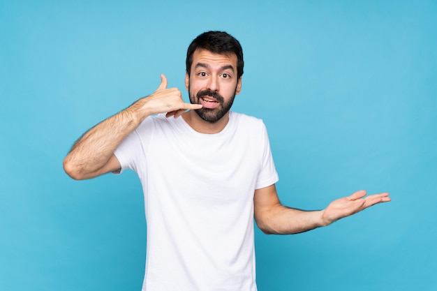 Young man with beard  over isolated blue making phone gesture and doubting