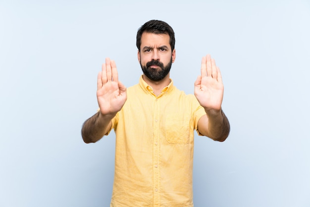 Young man with beard over isolated blue   making stop gesture and disappointed
