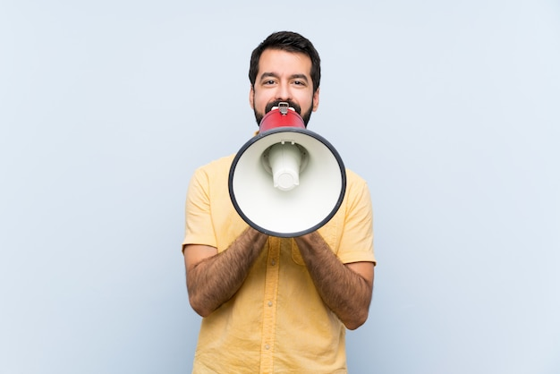 Young man with beard over isolated blue  shouting through a megaphone