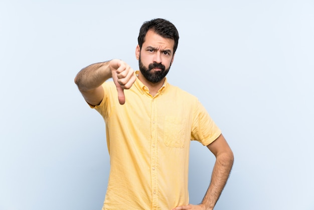 Young man with beard over isolated blue   showing thumb down with negative expression