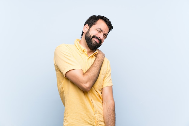 Young man with beard over isolated blue  suffering from pain in shoulder for having made an effort