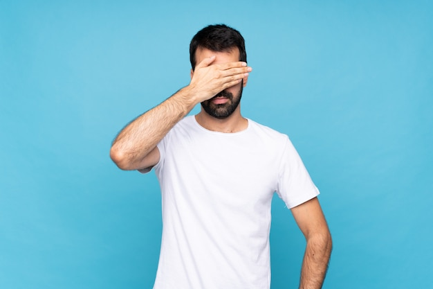 Young man with beard  over isolated blue wall covering eyes by hands. do not want to see something