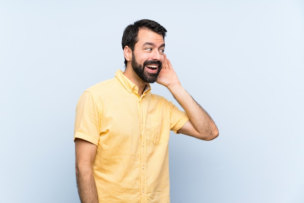 Young man with beard over isolated blue wall listening to something by putting hand on the ear
