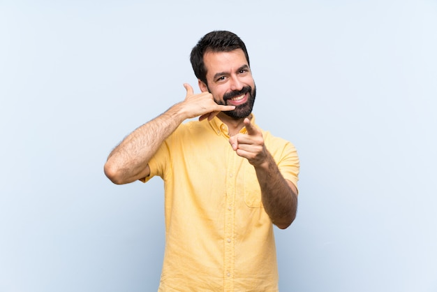 Young man with beard over isolated blue wall making phone gesture and pointing front