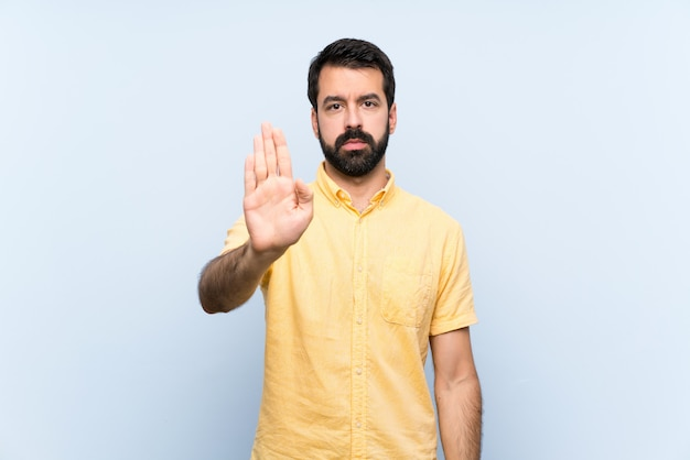 Young man with beard over isolated blue wall making stop gesture