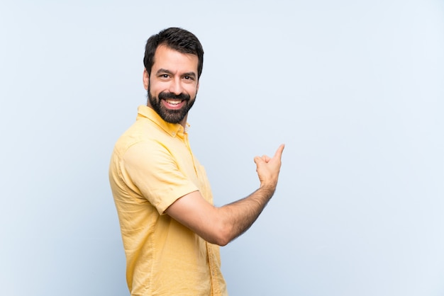 Young man with beard over isolated blue wall pointing back