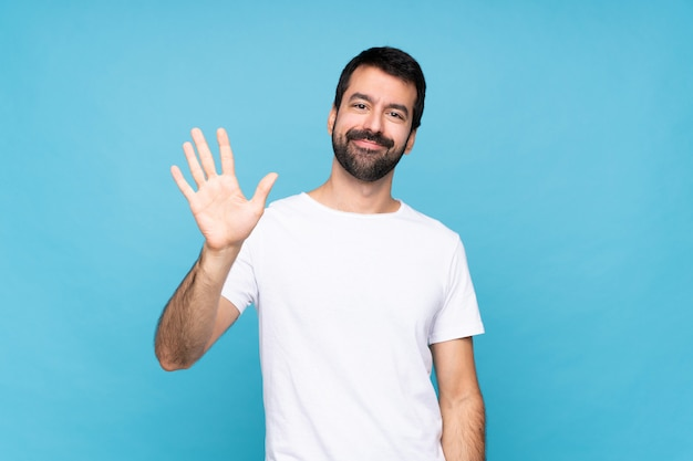 Young man with beard  over isolated blue wall saluting with hand with happy expression