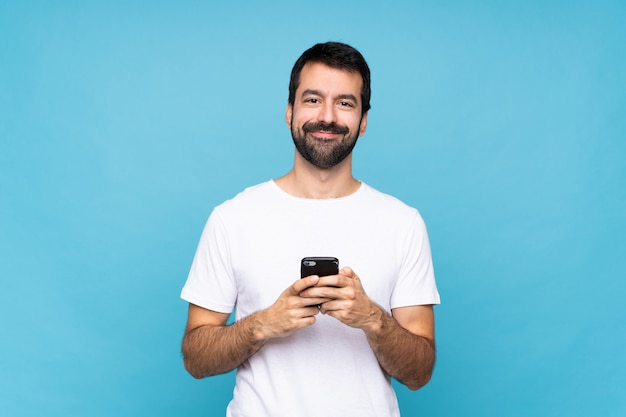 Young man with beard  over isolated blue wall sending a message with the mobile