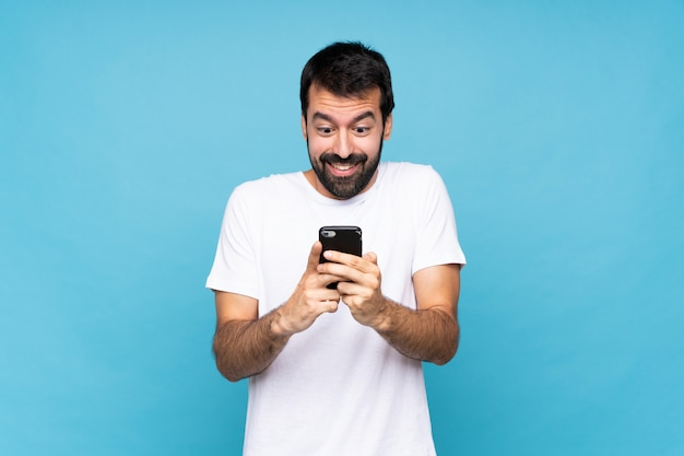 Young man with beard  over isolated blue wall surprised and sending a message