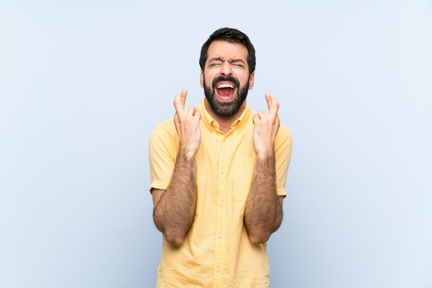 Young man with beard over isolated blue wall with fingers crossing