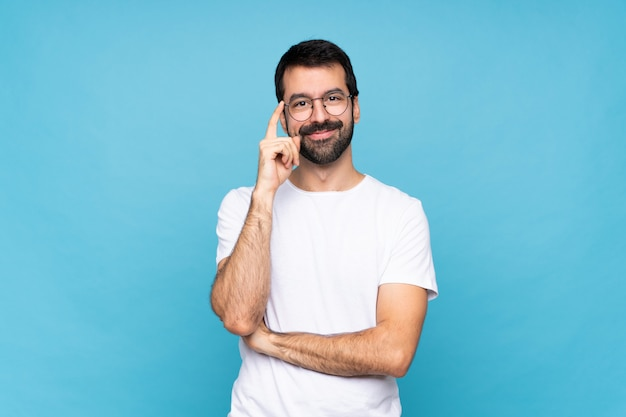 Young man with beard  over isolated blue wall with glasses and happy