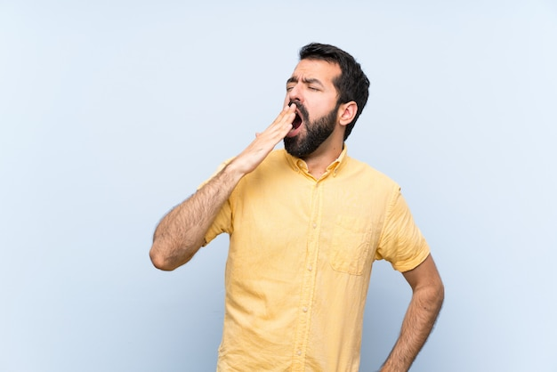 Young man with beard over isolated blue wall yawning and covering wide open mouth with hand