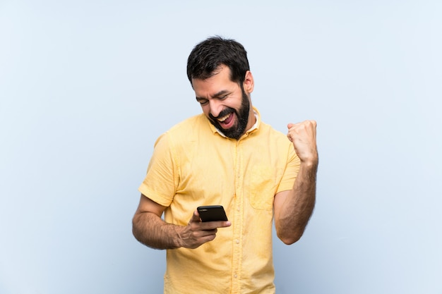 Young man with beard over isolated blue  with phone in victory position